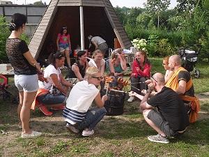fotografie - děti sedící v kruhu u ohně s buřty